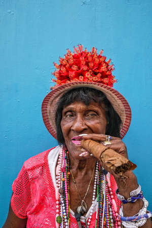 Havana, Cuba - May 06, 2017; A cuban woman holding a huge cigar in order to smoke in Havana, Cuba.