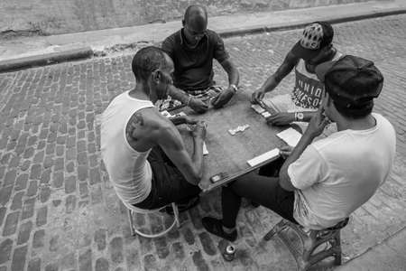 Havana, Cuba - May 01, 2017; Cuban men playing game of dominoes that is very popular in all Cuba. Black and white