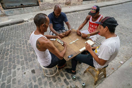 Havana, Cuba - May 01, 2017; Cuban men playing game of dominoes that is very popular in all Cuba.