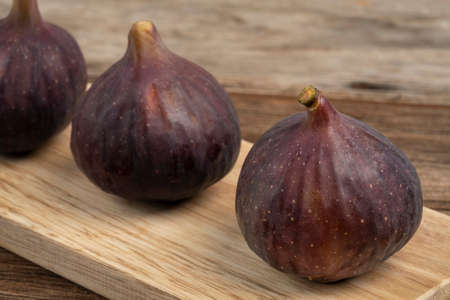ripe purple figs on a wooden table with copy space