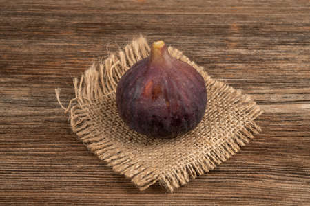 A ripe purple fig on a wooden table