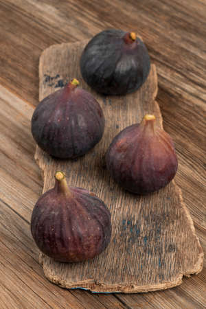 ripe purple figs on a wooden table