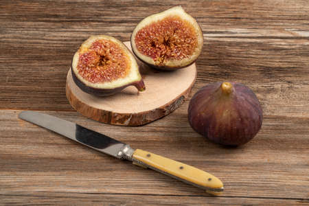 cut into half and whole ripe purple figs on a wooden table