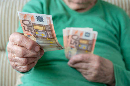 closeup wrinkled hand of a senior woman holding euro banknotes Stok Fotoğraf