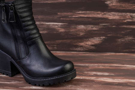 a new black leather boot on a wooden background with copy space