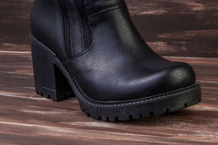 a new black leather boot on a wooden background with copy space Banco de Imagens