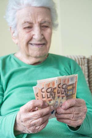 Closeup of a senior woman counting Euro banknotes