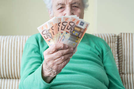 closeup hand of a senior woman holding euro banknotes with copy space Stok Fotoğraf