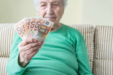 A senior woman looking to Euro banknotes in her wrinkled hand
