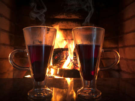 two glass of hot wines against flames of a fireplace