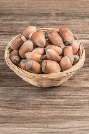 raw hazelnuts in a basket on wooden table with copy space Фото со стока