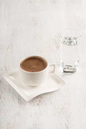Turkish coffee served with a glass of water on a wooden table