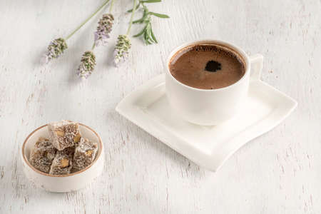 Cup of coffee served with Turkish delight on a wooden table Фото со стока