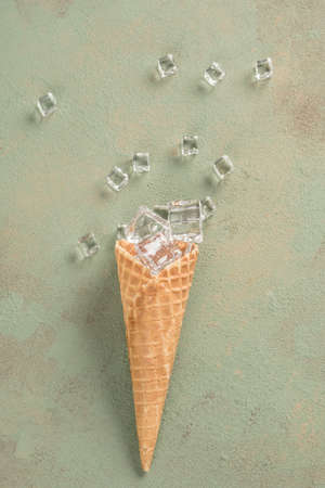 ice cubes in a ice cream cone on green background with copy space Фото со стока