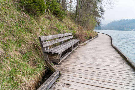 an empty old wooden bench at a park by sea