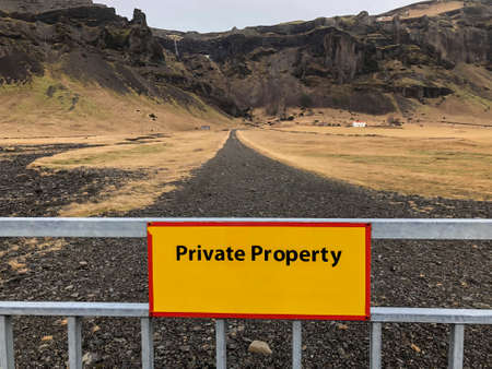private property sign on a fence against the road and land