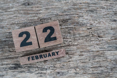 cube calendar for february on a wooden background with copy space