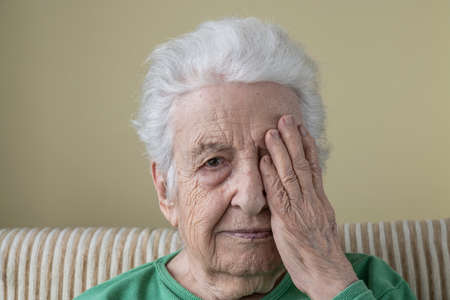 closeup face of a senior woman her one eye with her wrinkled hand Stock Photo