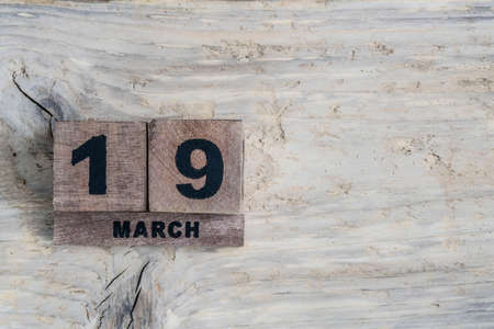 cube calendar for march on a wooden background with copy space