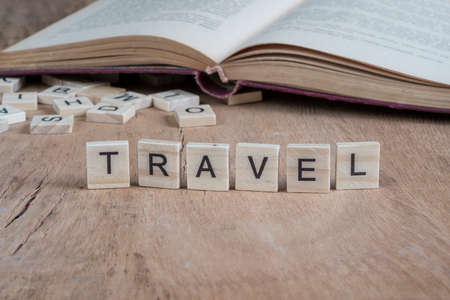 the word travel written with cube letters on wooden background Standard-Bild
