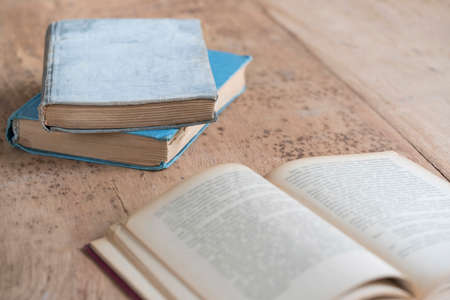 old hard covered books and an opened one on a wooden table with copy space