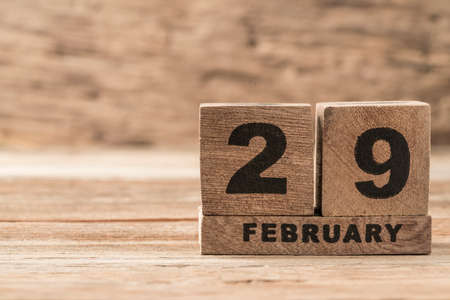 closeup cube calendar for february on wooden background with copy space