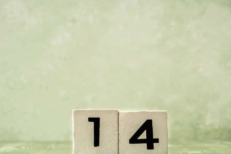 number fourteen with white wooden cubes over green with copy space Stock Photo