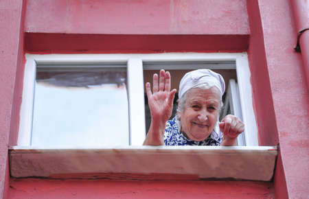 A happy senior woman waving her hand from the window of her apartment