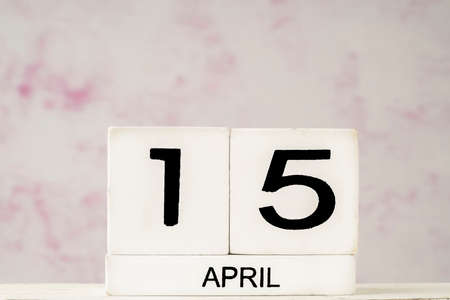 cube calendar for april against pink and white background with copy space