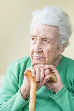 closeup of a senior woman leaning on a wooden cane
