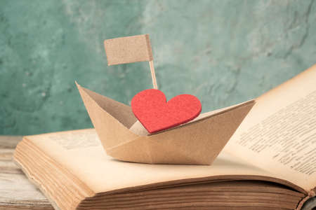 Folded paper sailing boat and red heart on old opened book on table. Hand crafted origami paper sailing boat on an opened book