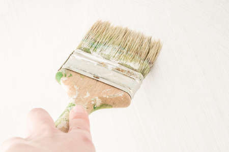 closeup hand painting a wooden surface with a brush