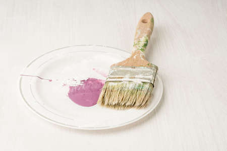 an used paint brush on a white wooden background Stockfoto