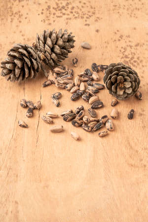 natural pine nuts, kernels and cone on a wooden table