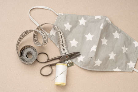 closeup of tailor made textile health mask with sewing tools