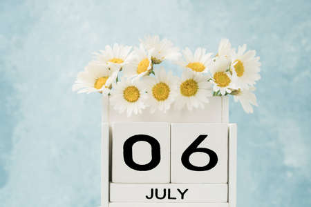 White cube calendar for july decorated with daisy flowers over blue background with copy space