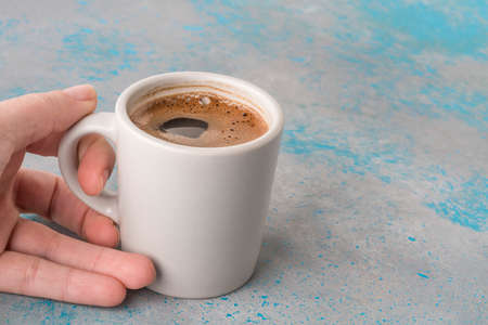 closeup hand of a woman holding a cup of Turkish coffee
