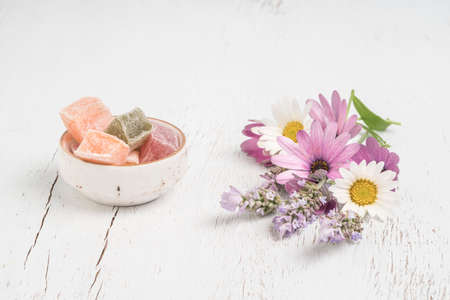 colorful Turkish delights and spring flowers on a wooden table with copy space