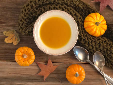 closeup pumpkin soup on a wooden table decorated with dried autumn leaves Zdjęcie Seryjne