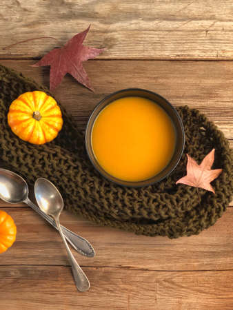 closeup pumpkin soups on a wooden table decorated with dried autumn leaves
