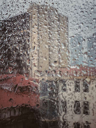 background with rain drops on window pane against buildings in a rainy day