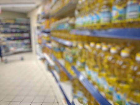 blurred background with supermarket shelves that full of oil bottles
