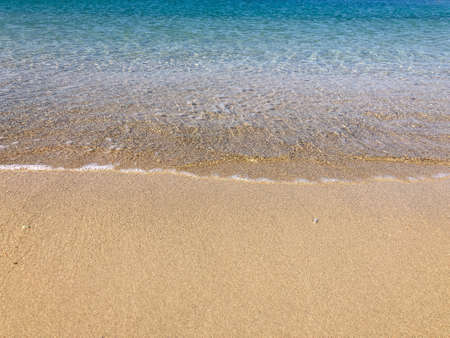 smooth waves of the sea on a sandy beach in summer with copy space