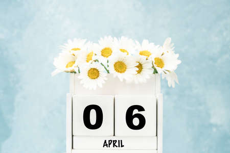 White cube calendar for April with daisy flowers over blue background with copy space