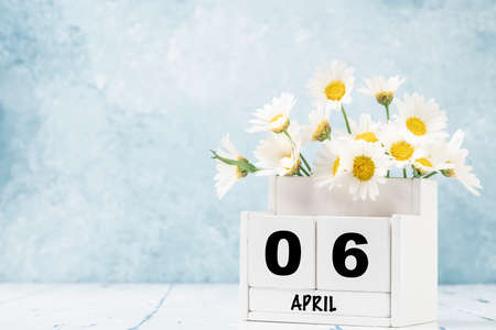 White cube calendar for april decorated with daisy flowers over blue background with copy space