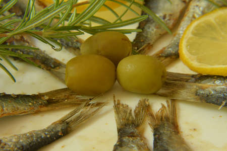engraulis encrasicolus: Anchovy with lemon, rosemary and olives on plate Stock Photo