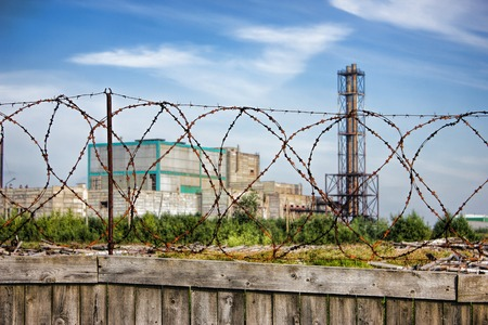 private security: Restricted area - wooden fence with barbed wire, plant in the background Stock Photo
