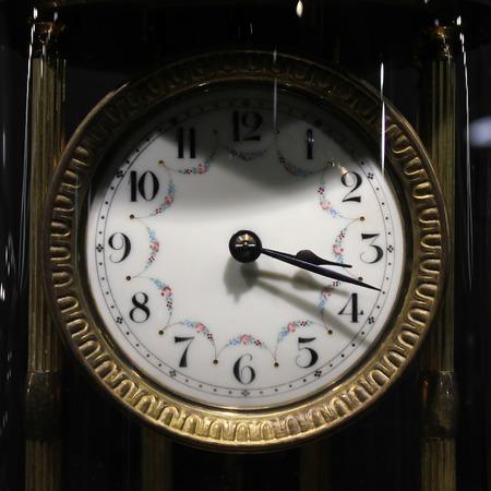 aging face: Old vintage antique clock on black background.