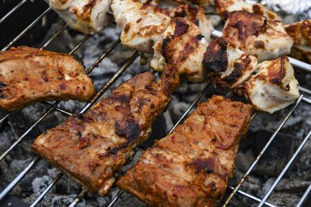 Juicy Pork steak, ribs and chicken meat on bbq grill, homemade barbecue, closeup.