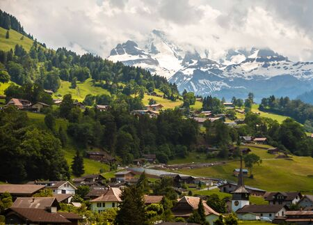 Amazing view of the hillside village and snowy slopes of the Swiss Alps. Colorful summer view of village. Idyllic outdoor scene in Switzerland, Europe